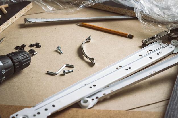 Outils pour l'assemblage de meubles, détails de meubles, film d'emballage, vis sur une feuille de carton. construction manuelle de meubles. atelier conceptuel