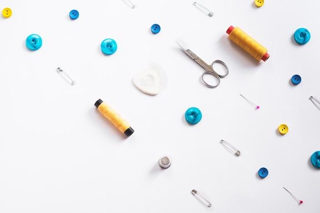 Outils pour la coupe et la couture. trousse de couturière. bobines multicolores de fils, ruban adhésif, aiguilles sur fond blanc