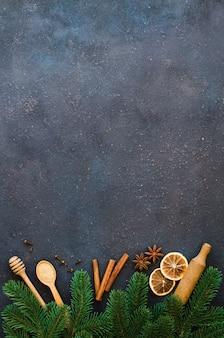 Outils pour la cuisson et branches de sapin sur béton.