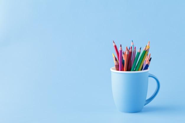Outils pour dessiner, tas de crayons de couleur sur bleu