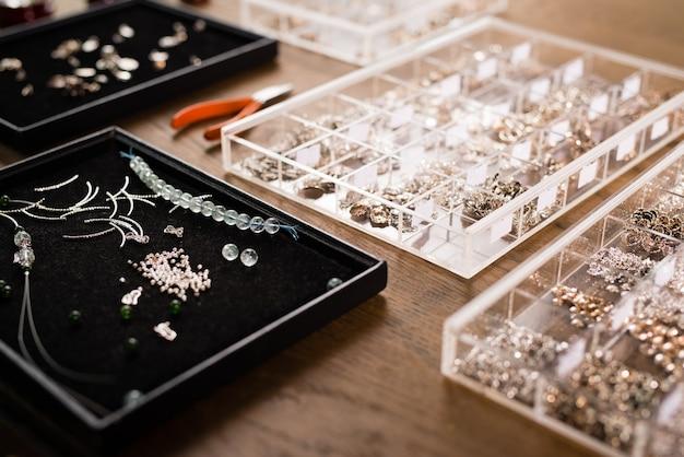 Outils pour la fabrication de bijoux, perles de pierre colorées. lieu de travail de bijouterie.