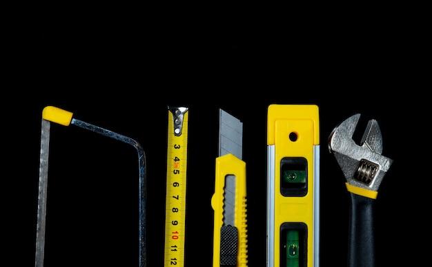Outils pour maître constructeur sur fond noir. gros plan de l'outil de construction. vue de dessus