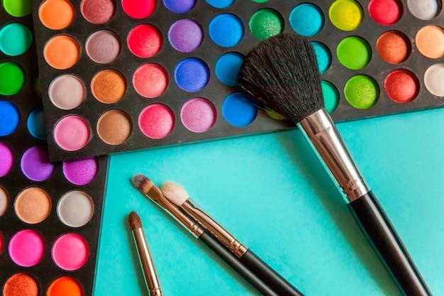 Outils pour le maquillage et les cosmétiques différentes nuances de palette de fard à paupières et pinceau de maquillage sur la table pastel bleu coloré à la mode. vue de dessus à plat