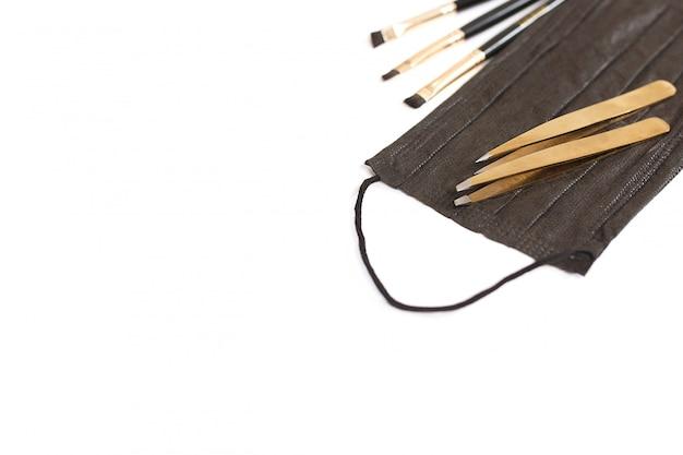 Outils pour la mise en forme des sourcils. masque, pince à épiler, pinceaux. vue de dessus, place pour le texte.