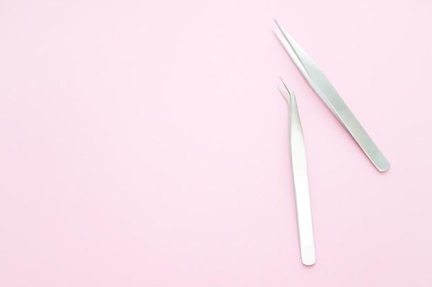 Outils pour la procédure d'extension des cils. deux pincettes sur fond rose.