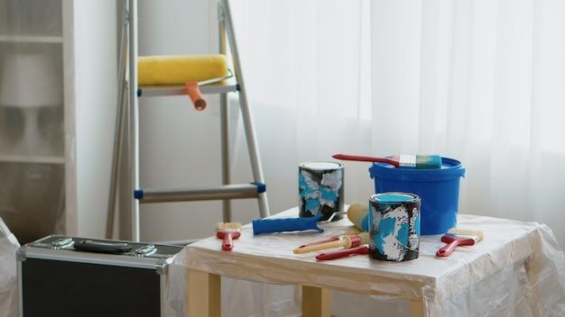 Outils pour la rénovation domiciliaire. pots de peinture, pinceau, rouleau. maison en cours de rénovation, décoration et peinture. entretien de l'amélioration de l'intérieur de l'appartement. rouleau, échelle pour la réparation de la maison