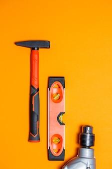 Outils pour la réparation d'un usage domestique. marteau pour clous, niveau et perceuse sur fond orange. boîte à outils pour l'assistant