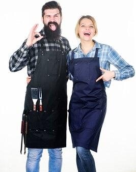Outils pour rôtir la viande. un couple amoureux tient des ustensiles de cuisine. homme barbu hipster et fille. préparation et culinaire. barbecue pique-nique. recette de cuisine alimentaire. week-end en famille. trop bon.