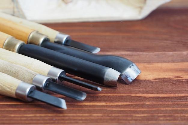 Outils pour sculpter sur des planches en bois sombres. arborescence
