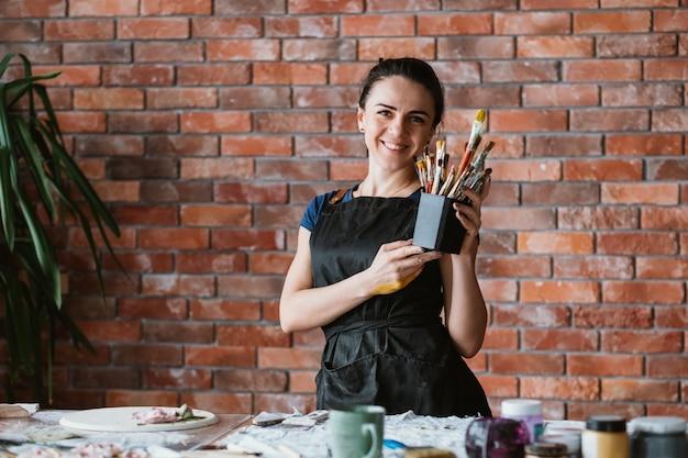 Des outils pour les talents artistiques. lieu de travail de femme peintre. belle femme souriante en tablier posant avec des pinceaux.