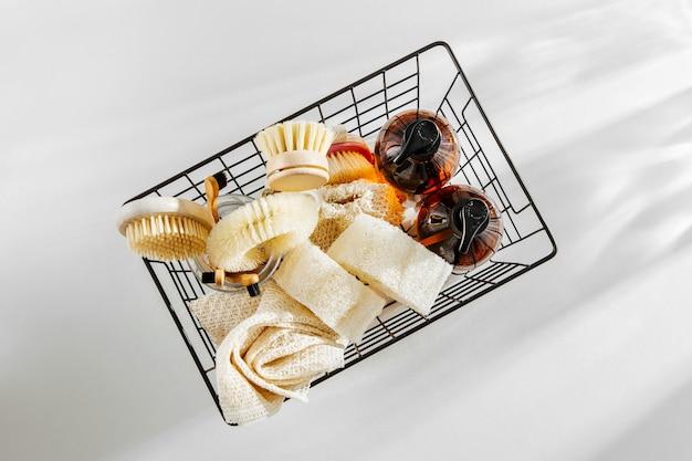 Outils et produits de nettoyage naturels écologiques, brosses à vaisselle en bambou et savon dans un panier en métal noir. concept zéro déchet. sans plastique. mise à plat, vue de dessus