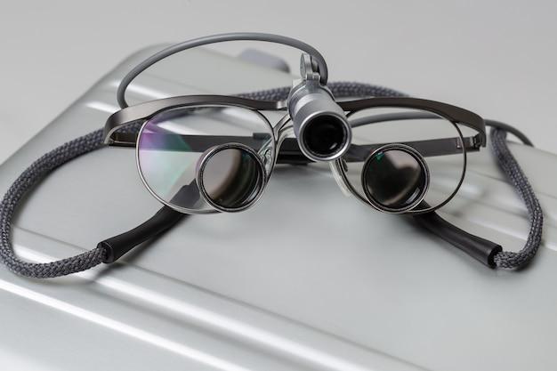 Outils professionnels loupe binoculaire dentaire éclairée sur boîtier métallique gros plan