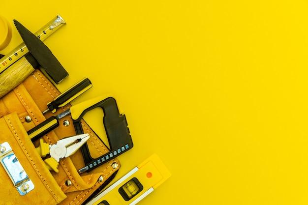 Outils professionnels pour le menuisier et pièces de rechange. ensemble pour le maître sur fond jaune.