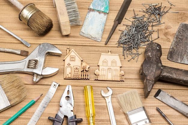 Outils de réparation à domicile pour les travaux de réparation et de restauration manuels, outils anciens et poussiéreux. fond en bois clair. mise à plat