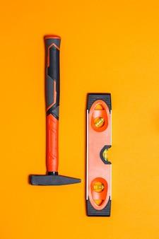 Outils de réparation. marteau pour clous et niveau sur fond orange. boîte à outils pour l'assistant
