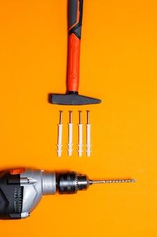 Outils de réparation. marteau pour clous, perceuse, goujon dans le mur sur fond orange. boîte à outils pour l'assistant