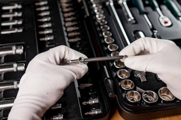 Outils de réparation de voiture dans les mains des hommes en gros plan sur la boîte à outils avec instruments mécaniques