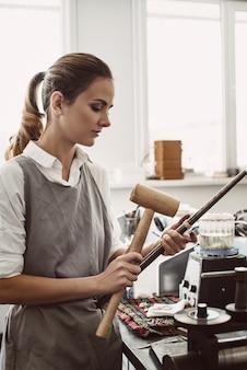 Des outils simples. vue latérale d'une créatrice de bijoux pliant un blanc d'argent sur la route à l'aide d'un marteau maillet dans son atelier.