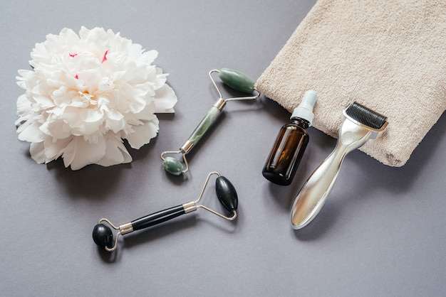 Outils de soin de la peau : rouleau de derma microneedling, rouleaux de massage jade guasha et bouteille de sérum sur fond gris avec fleur de pivoine blanche