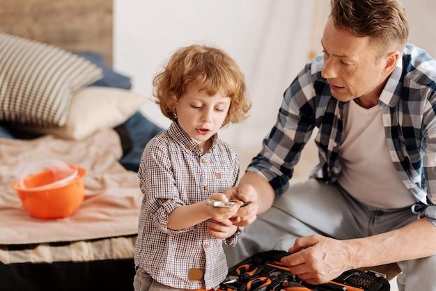Outils spéciaux. père sérieux plissant son front et assis près de son fils tout en tenant la clé dans la main droite