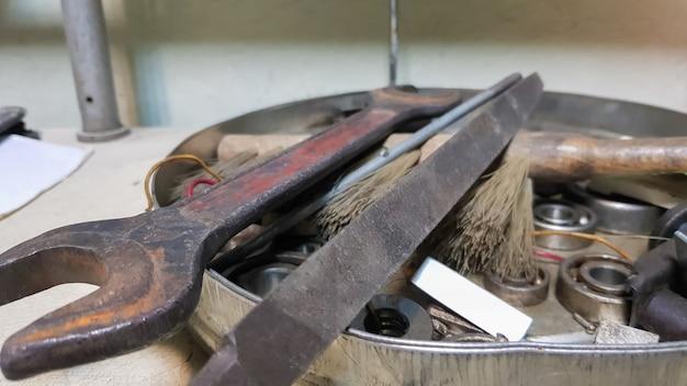 Outils de travail au tableau et en atelier. scène d'atelier. beaucoup de vieux outils sur un bureau sale. le concept de menuiserie et de peinture.