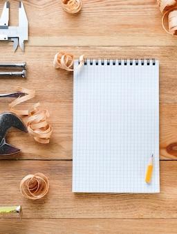 Outils de travail, bloc-notes et café sur une table en bois. outils de construction sur des planches en bois. concept de construction.