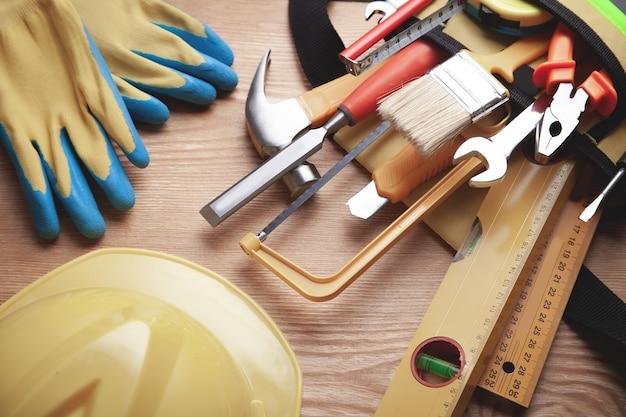 Outils de travail avec casque et gants sur fond en bois.