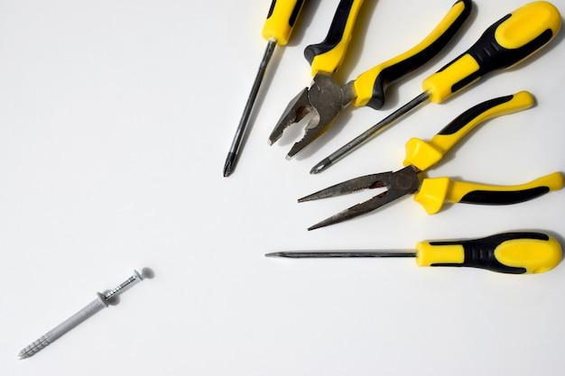 Outils de travail noirs et jaunes, pinces, coupe-fils, goujons et tournevis. compétition, combat, combat, bataille, agressif