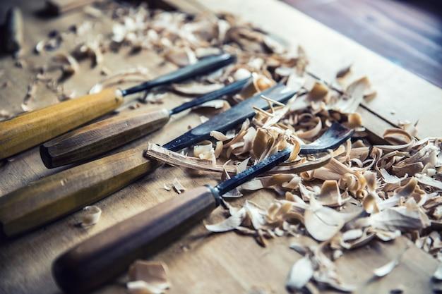 Outils vintage de travail du bois ciseaux avec des shawings en bois sur un établi rétro.