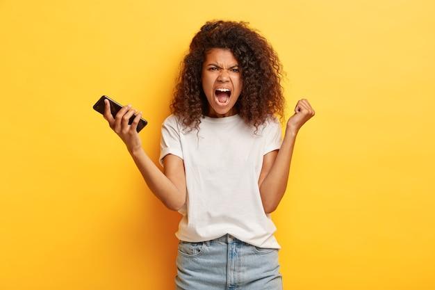 Outragé jeune femme aux cheveux bouclés posant avec son téléphone