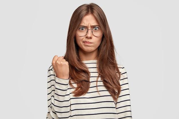 Outragé jeune femme avec des lunettes posant contre le mur blanc