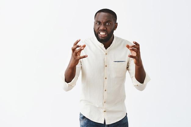 Outragé jeune homme posant contre le mur blanc