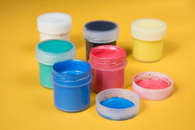 Ouvert des bouteilles de peinture aquarelle sur du papier jaune