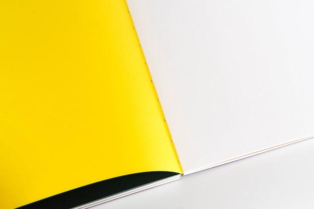 Ouvert le livre blanc au fond de papier de conception jaune blanc.