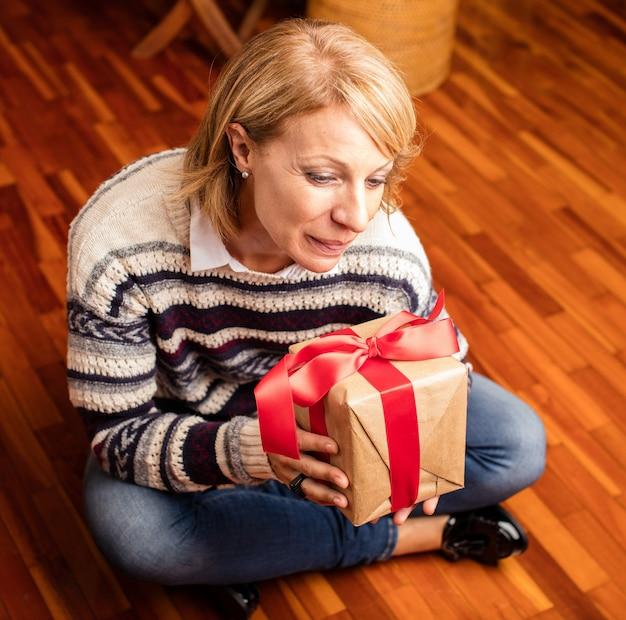L'ouverture d'un cadeau de noël heureuse mère