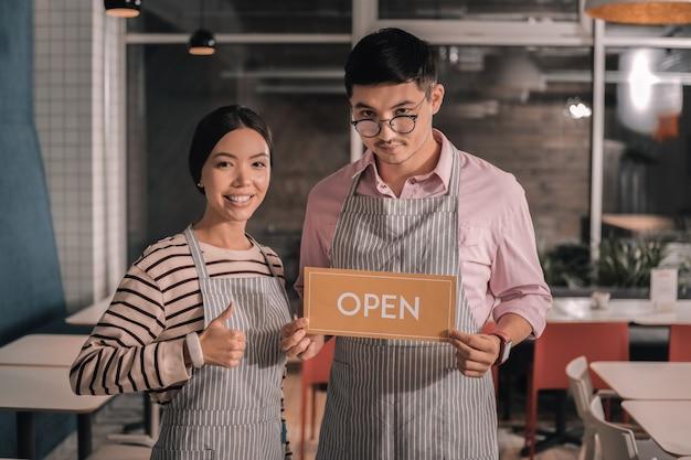 Ouverture de la cafétéria. couple d'entrepreneurs prometteurs ouvrant leur propre petite cafétéria confortable