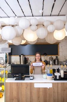 Une ouverture d'une jeune femme souriante l'ouverture d'un nouveau café