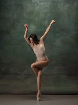 Ouvrages d'art. ballerine classique gracieuse dansant sur fond de studio sombre. body pastel. le concept de grâce, d'artiste, de mouvement, d'action et de mouvement. semble en apesanteur, flexible. style de mode.