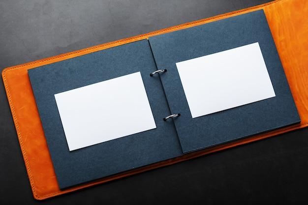 Ouvrez l'album photo avec un espace vide pour les photos, des cadres blancs sur du papier noir. la pochette de l'album est en cuir véritable marron fait main