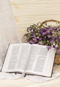 Ouvrez la bible et le bouquet de lin dans un panier en osier. style rétro, vintage