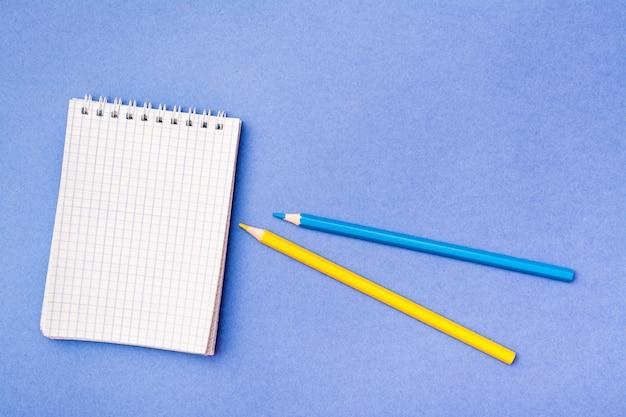 Ouvrez le bloc-notes dans une cage sur une spirale, des crayons jaunes et bleus sur un bleu