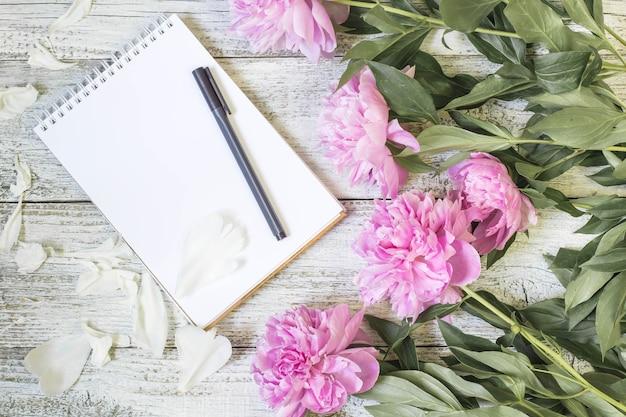 Ouvrez le bloc-notes vierge, le stylo et la pivoine sur la table en bois blanche. mise à plat romantique.