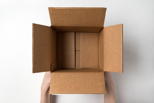Ouvrez une boîte en carton vide dans des mains féminines. vue de dessus