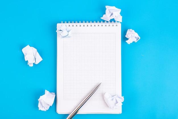 Ouvrez un cahier blanc vierge avec un stylo sur un tableau bleu. concept d'entreprise