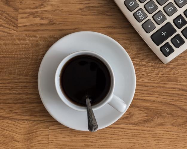 Ouvrez un cahier blanc vierge, un stylo et une tasse de café et une calculatrice
