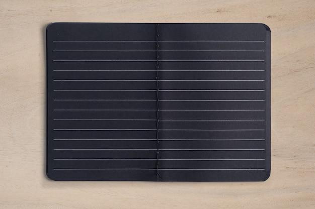 Ouvrez le cahier noir blanc sur la table en bois