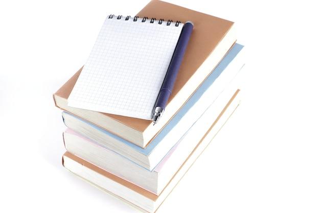 Ouvrez le cahier, le stylo et une pile de livres sur blanc