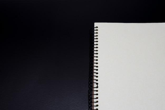 Ouvrez la demi-vue du cahier sur un fond sombre et rugueux avec un espace de copie