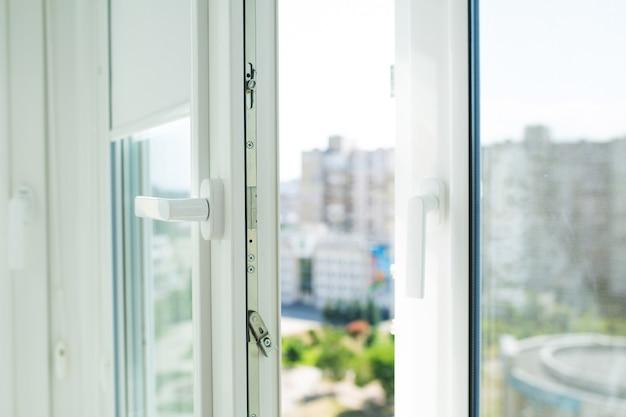 Ouvrez la fenêtre en plastique en métal avec le fond brouillé de ville
