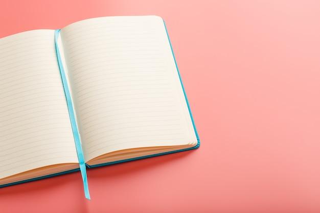 Ouvrez un ordinateur portable avec des pages blanches sur fond rose. vue de dessus, espace copie